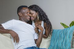 Young beautiful and happy black afro American couple in love relaxed at home living room sofa couch smiling cheerful having fun. Relaxed and homey in successful stock image