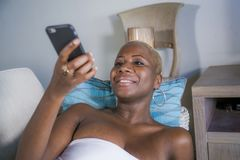 Young beautiful and happy black afro american woman lying at home couch relaxed smiling cheerful using internet social media app o. N mobile phone dating or royalty free stock images