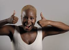 Young beautiful and happy black afro American woman smiling giving ok thumb up sign looking positive and playful in cool exotic sh. Aved head hair style in good Royalty Free Stock Photo