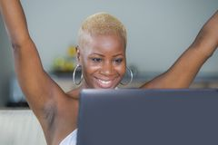 Young beautiful happy black afro American woman smiling working on laptop computer at home relaxed on sofa couch celebrating succe royalty free stock image