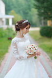 Young beautiful happy bride with flower bouquet in park Royalty Free Stock Photos