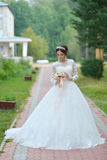 Young beautiful happy bride with flower bouquet in park Stock Image
