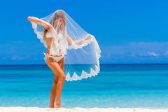 Young beautiful happy bride in white bikini holding flower bouqu Royalty Free Stock Images