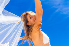 Young beautiful happy bride in white bikini holding flower Royalty Free Stock Photo