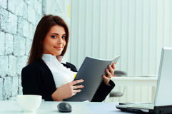 Young beautiful happy businesswoman holding the notebook Stock Images