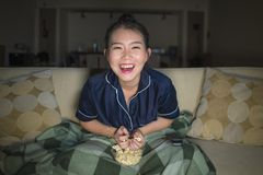 Young beautiful happy and cheerful Asian Japanese woman watching TV comedy movie or hilarious show laughing and eating popcorn stock photography