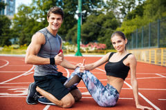 Young beautiful happy couple doing exercises at the stadium Stock Image