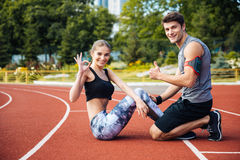 Young beautiful happy couple doing sports exercises at the stadium Royalty Free Stock Photography
