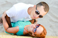 Young beautiful happy couple embracing on sandy beach Royalty Free Stock Photos