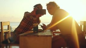 Young beautiful couple in love takes selfie with smartphone in beach cafe drinking beer during sunset time in slowmotion stock video footage
