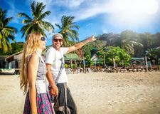Young beautiful happy couple walking along the shore of the trop Royalty Free Stock Image