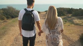Young beautiful couple walking on the sand road near the sea side and holding hands. Young beautiful happy couple walking on the sand road near the sea side and stock footage