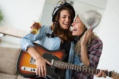 Young happy dancing girls playing guitar and partying. Young beautiful happy dancing girls playing guitar and partying Royalty Free Stock Image
