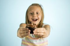 Young beautiful happy and excited blond girl 8 or 9 years old holding chocolate cake on her hand looking spastic and cheerful in s. Ugar calories and unhealthy stock photography