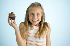 Young beautiful happy and excited blond girl 8 or 9 years old holding chocolate cake on her hand looking spastic and cheerful in s. Ugar calories and unhealthy royalty free stock photography