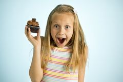 Young beautiful happy and excited blond girl 8 or 9 years old holding chocolate cake on her hand looking spastic and cheerful in s. Ugar calories and unhealthy stock image