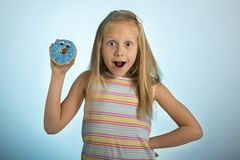 Young beautiful happy and excited blond girl 8 or 9 years old holding donut desert on her hand looking spastic and cheerful in sug. Young beautiful happy and stock photo