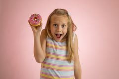Young beautiful happy and excited blond girl 8 or 9 years old holding donut desert on her hand looking spastic and cheerful in sug. Young beautiful happy and royalty free stock photo