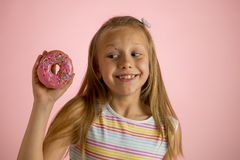 Young beautiful happy and excited blond girl 8 or 9 years old holding donut desert on her hand looking spastic and cheerful in sug. Young beautiful happy and stock photography