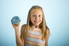 Young beautiful happy and excited blond girl 8 or 9 years old holding donut desert on her hand looking spastic and cheerful in sug. Young beautiful happy and royalty free stock images