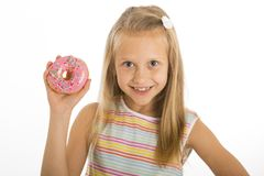 Young beautiful happy and excited blond girl 8 or 9 years old holding donut desert on her hand looking spastic and cheerful in sug. Young beautiful happy and stock images