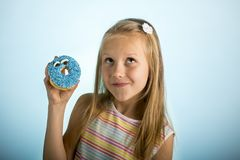Young beautiful happy and excited blond girl 8 or 9 years old holding donut desert on her hand looking spastic and cheerful in sug. Young beautiful happy and stock photos