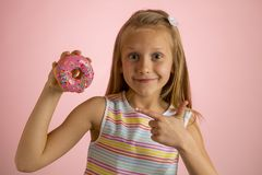 Young beautiful happy and excited blond girl 8 or 9 years old holding donut desert on her hand looking spastic and cheerful in sug. Young beautiful happy and royalty free stock image