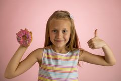 Young beautiful happy and excited blond girl 8 or 9 years old holding donut desert on her hand looking spastic and cheerful in sug. Young beautiful happy and stock image