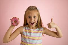 Young beautiful happy and excited blond girl 8 or 9 years old holding donut desert on her hand looking spastic and cheerful in sug. Young beautiful happy and royalty free stock photography