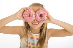 Young beautiful happy and excited blond girl 8 or 9 years old holding two donuts on her eyes looking through them playing cheerful. In sugar calories and royalty free stock photo