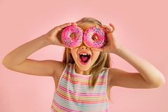 Young beautiful happy and excited blond girl 8 or 9 years old holding two donuts on her eyes looking through them playing cheerful. In sugar calories and stock photos
