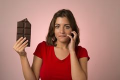 Young beautiful happy and excited woman holding big chocolate bar in sugar addiction temptation. Looking guilty skipping diet in unhealthy nutrition lifestyle Stock Photography