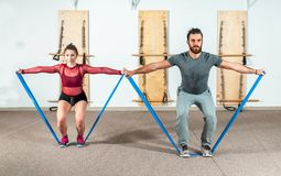 Young beautiful happy fitness couple workout yoga exercise with stretch rubber for long and healthy life, selective focus royalty free stock photos