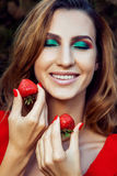 Young beautiful happy funny girl with red dress and makeup holding strawberry in summertime in the park. Stock Image