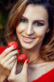 Young beautiful happy funny girl with red dress and makeup holding strawberry in summertime in the park. Stock Images