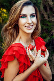 Young beautiful happy funny girl with red dress and makeup holding strawberry in summertime in the park. Stock Photography