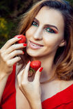Young beautiful happy funny girl with red dress and makeup holding strawberry in summertime in the park. Royalty Free Stock Image