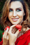 Young beautiful happy funny girl with red dress and makeup holding strawberry in summertime in the park. Royalty Free Stock Photography