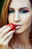 Young beautiful happy funny girl with red dress and makeup holding strawberry in summertime in the park. Stock Photo