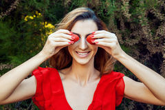 Young beautiful happy funny girl with red dress and makeup holding strawberry in summertime in the park. Royalty Free Stock Images