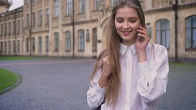 Young beautiful happy girl answers call during going from university in daytime in summer, communication conception.  stock video