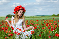 Young beautiful happy girl with long hair in a white dress in the poppy field with a wreath on his head Stock Photography