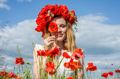 Young beautiful happy girl with long hair in a white dress in the poppy field with a wreath on his head Royalty Free Stock Photo