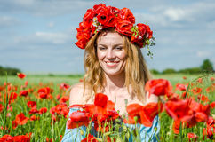 Young beautiful happy girl with long hair in a white dress in the poppy field with a wreath on his head Royalty Free Stock Images