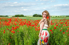 Young beautiful happy girl with long hair in a white dress in the poppy field with a wreath on his head Royalty Free Stock Photography