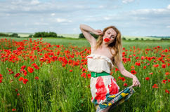 Young beautiful happy girl with long hair in a white dress in the poppy field with a wreath on his head Stock Photos
