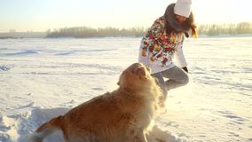 Young beautiful happy girl plays with a retriever dog in the snow in winter in sunny day during sunset time Stock Photo