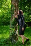 A young happy woman poses in a forest in the grass next to a tree on a sunny spring day stock images