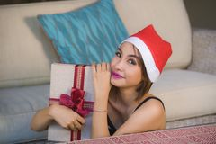 Young beautiful and happy girl in Santa hat holding Christmas present box with ribbon smiling cheerful and excited at home couch r royalty free stock images