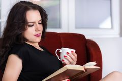 Young cute happy woman sitting in red armchair and reading book stock photo